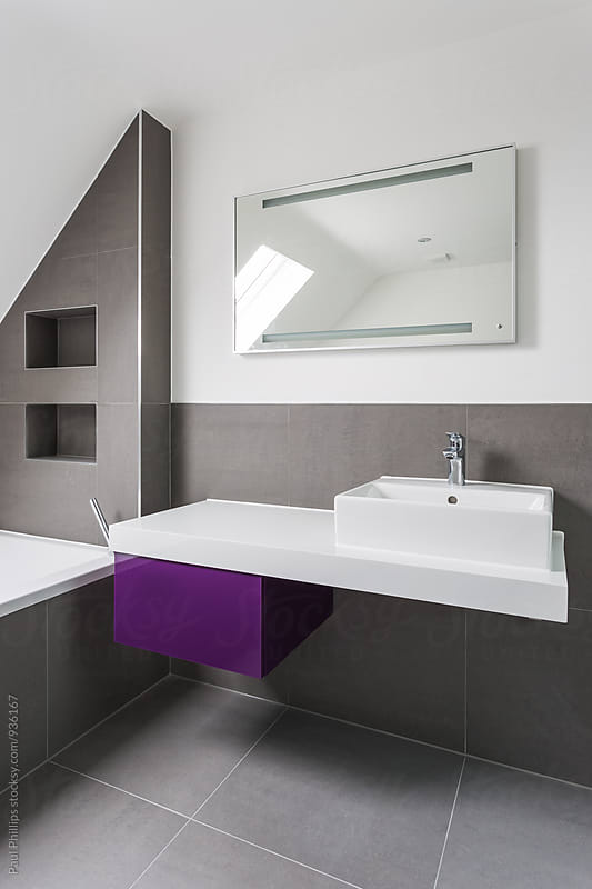 Corner of a contemporary bathroom with a white wash basin and purple vanity unit. by Paul Phillips for Stocksy United