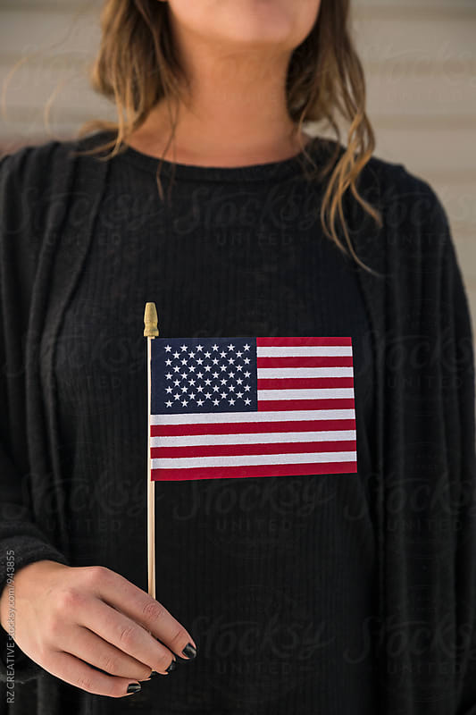 Woman holding U.S. flag. by Robert Zaleski for Stocksy United