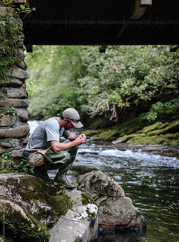 Man crouching and trying lure while fly-fishing near bridge by Matthew Spaulding for Stocksy United