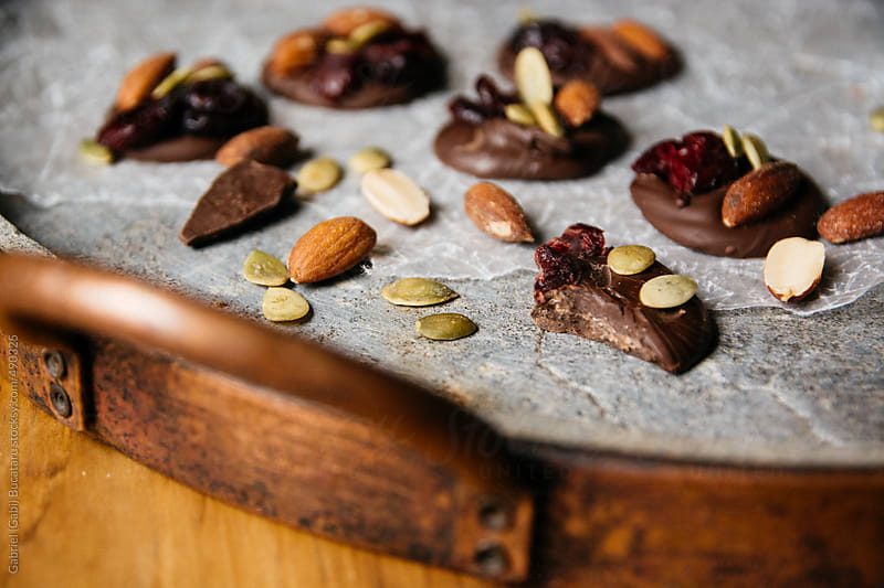 Chocolate with cranberry, pumpkin seeds, and almonds in a stone tray by Gabriel (Gabi) Bucataru for Stocksy United