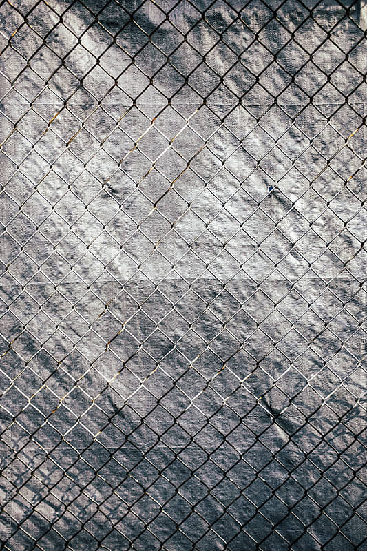 Chainlink fence in front of silver tarp by Paul Edmondson for Stocksy United