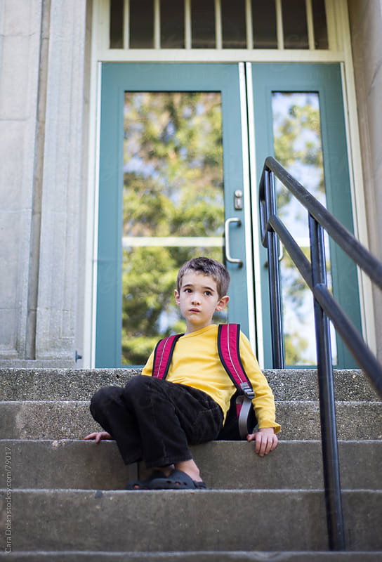 Boy is scared as he sits on the steps outside a school by Cara Dolan for Stocksy United