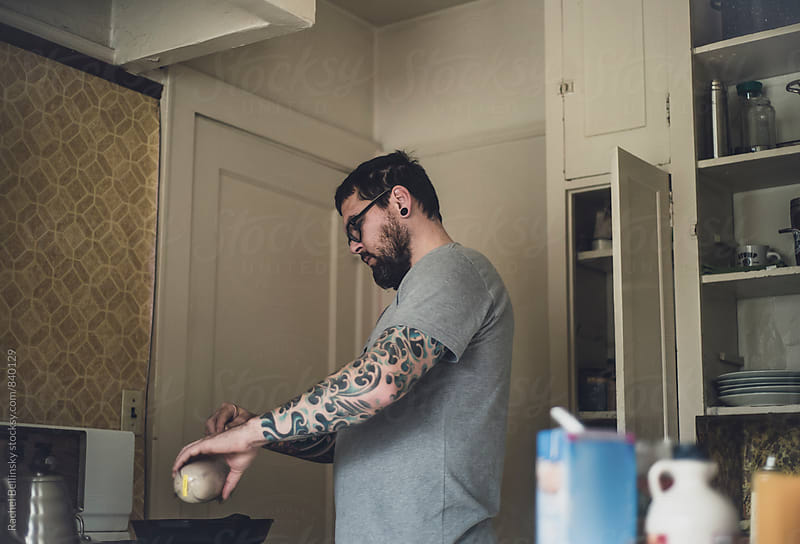 A handsome tattoo'd man cooks in his kitchen by Rachel Bellinsky for Stocksy United