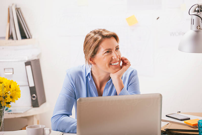 Smiling beautiful mature business woman working with laptop at home office. by BONNINSTUDIO for Stocksy United