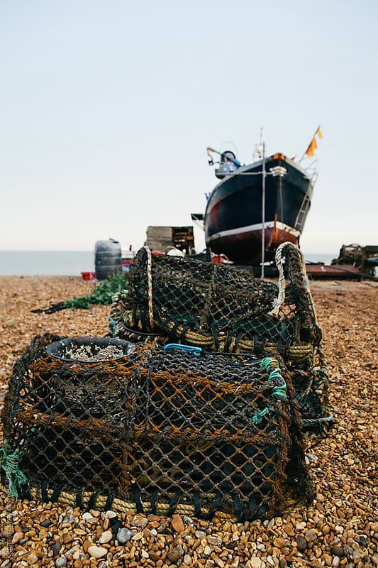 Lobster pots and fishing boat on a quiet beach in Kent. by kkgas for Stocksy United