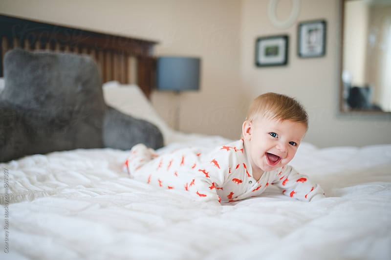 Happy baby on bed by Courtney Rust for Stocksy United