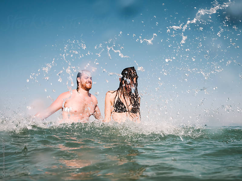 Friends having fun with water in the sea by GIC for Stocksy United