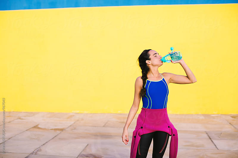 Woman wearing a wetsuit drinking water after workout. by BONNINSTUDIO for Stocksy United