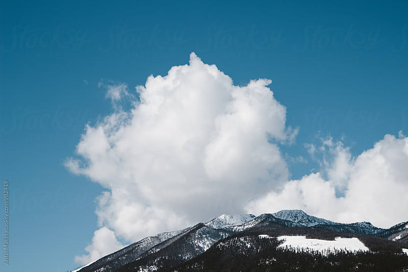 Big puffy white cloud over mountain top against bright blue sky by Justin Mullet for Stocksy United