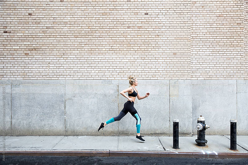 Woman running fast paced down a street by Ann-Sophie Fjelloe-Jensen for Stocksy United