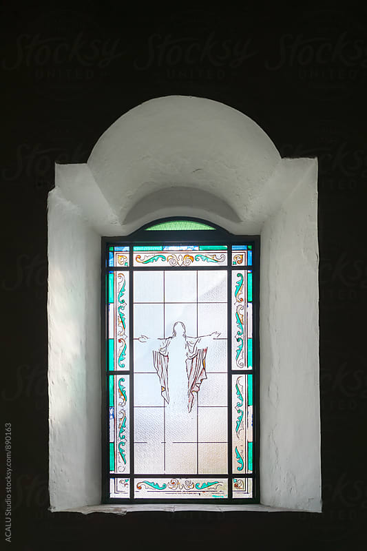 Window with a picture of a Christ with open arms by ACALU Studio for Stocksy United