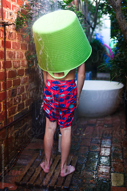 Boy standing under an outdoor shower with a green bucket on his head by Angela Lumsden for Stocksy United