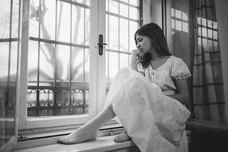 Beautiful woman in white dress by the window by Maja Topcagic for Stocksy United