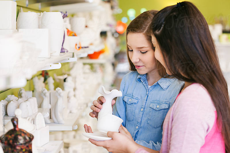Girl Friends Looking At Unpainted Ceramic Items by Sean Locke for Stocksy United