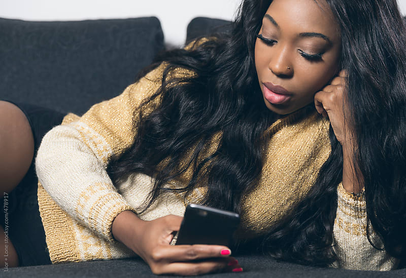 Young attractive black woman texting from her mobile phone by Lior + Lone for Stocksy United