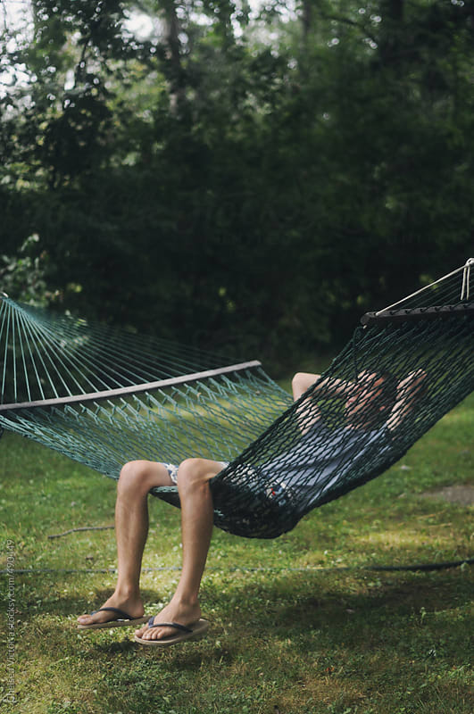 Man reclining on a hammock by Chelsea Victoria for Stocksy United