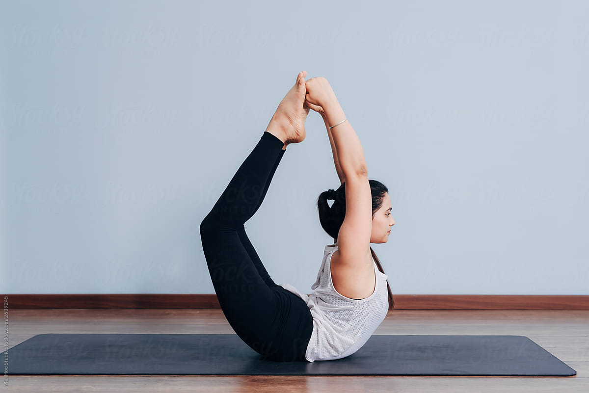 Pretty sporty Indian woman doing difficult yoga pose by MaaHoo