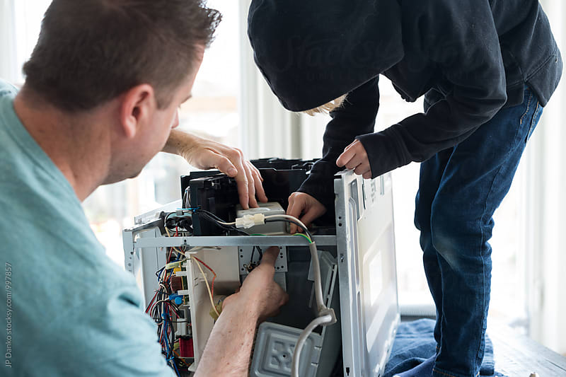 Father and Son Repairing Broken Microwave Oven Appliance In Kitchen by JP Danko for Stocksy United