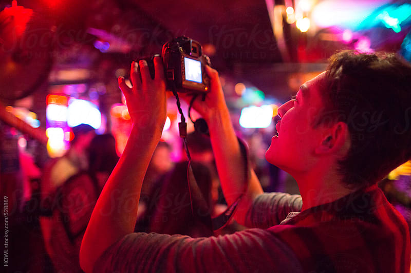 A fan takes a photographs of an act on stage by HOWL for Stocksy United