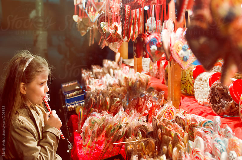 Girl buying lollips on candy market by Marija Anicic for Stocksy United
