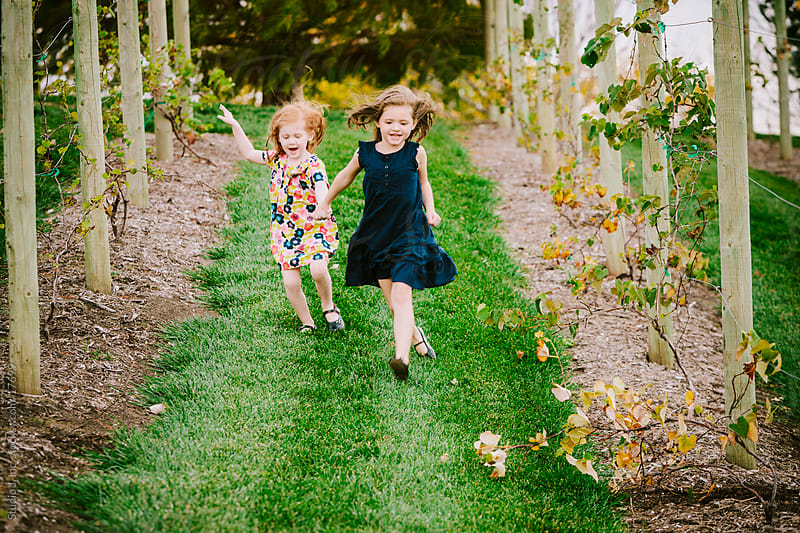 Little Girl Sisters Run Down a HIll Holding Hands by Jani Bryson for Stocksy United