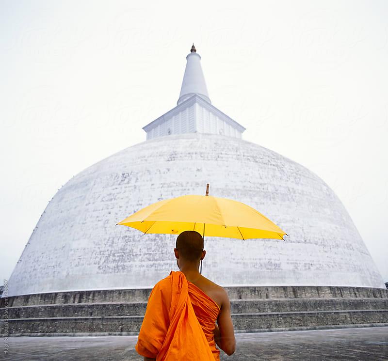 Buddhist monk holding umbrella standing in front of dagoba. Sri Lanka. by Hugh Sitton for Stocksy United