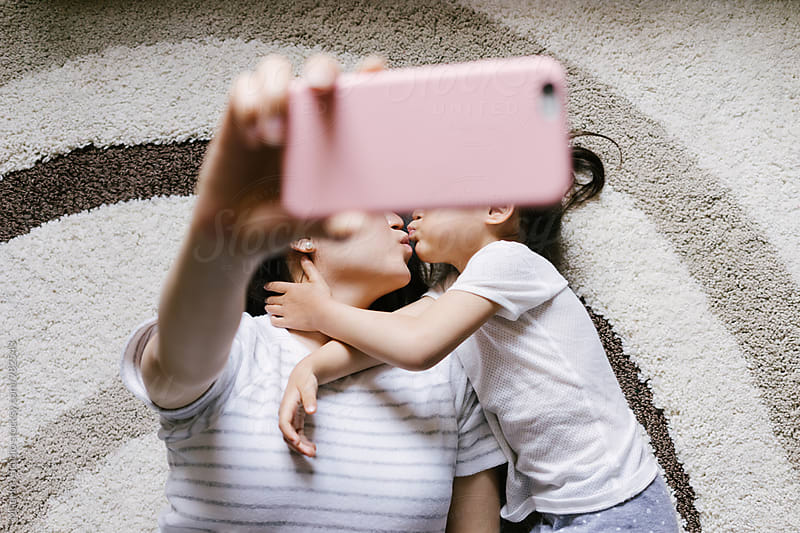 Adorable little girl with her mother taking selfie by MaaHoo Studio for Stocksy United