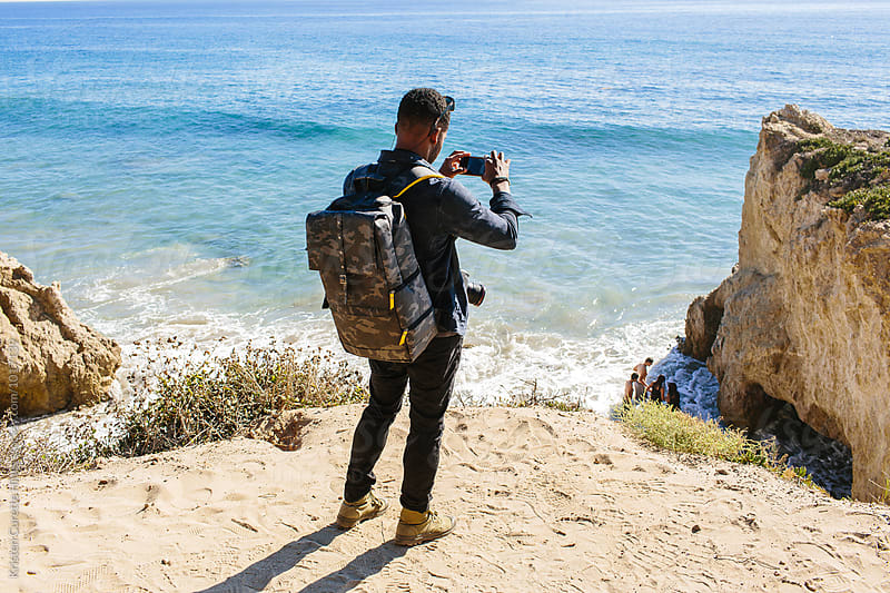 A man taking a photo of the beach in Cali.  by Kristen Curette Hines for Stocksy United