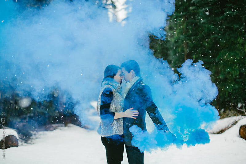 Young couple standing in snow with smoke grenade by Luke Liable for Stocksy United