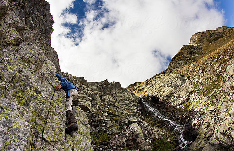 Young man climbing rock, waterfall in background by Marko Milovanović for Stocksy United