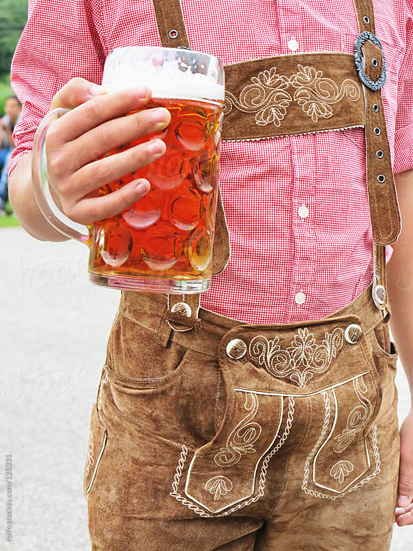 Man holding a glass of beer wearing German Bavarian clothes by rolfo for Stocksy United