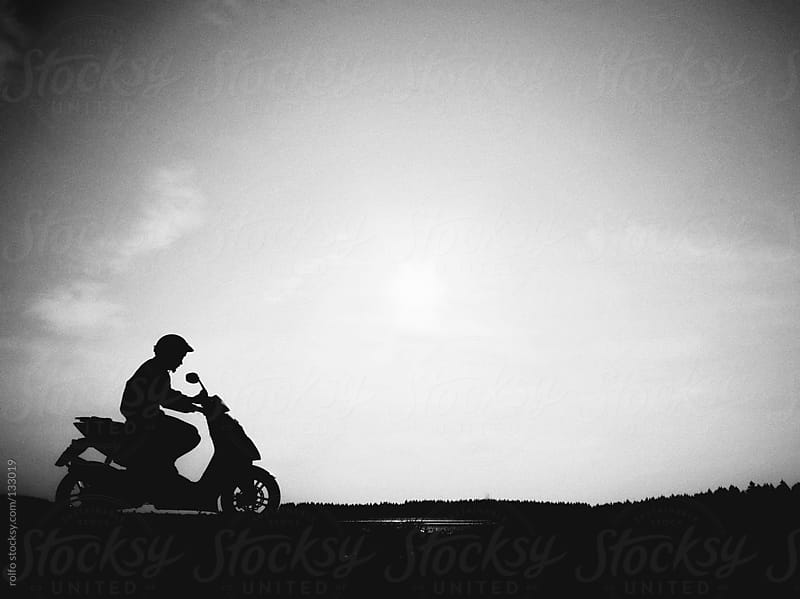Silhouette of a man riding a motor bike by rolfo for Stocksy United