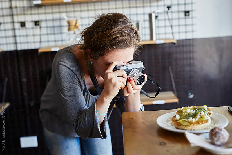 Woman taking photo of food in cafe with old camera by Martí Sans for Stocksy United