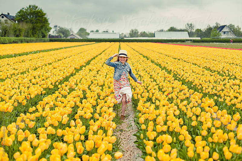 Little girl running through yellow flower field holding her hat by Cindy Prins for Stocksy United