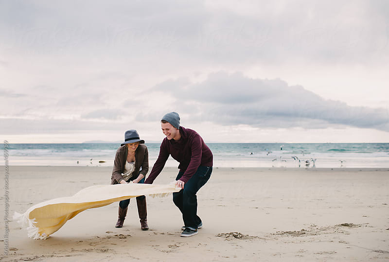 Couple on date putting blanket down on beach by Kristin Rogers Photography for Stocksy United