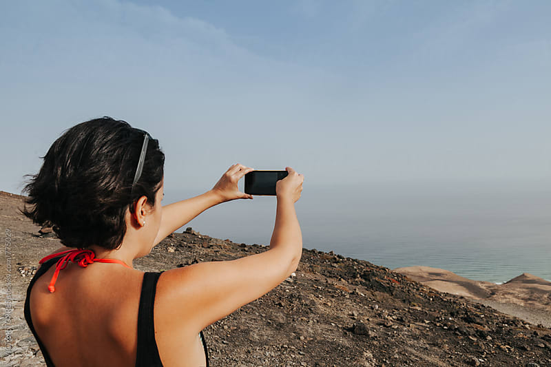 Young Woman Taking Photos to the Sea from a Viewpoint by VICTOR TORRES for Stocksy United