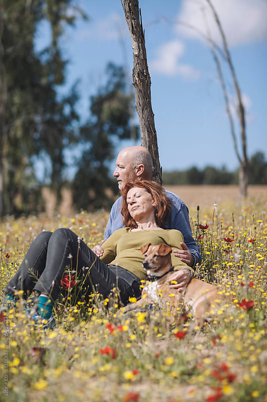 Man and woman in their 60's relaxing in nature by Lior + Lone for Stocksy United