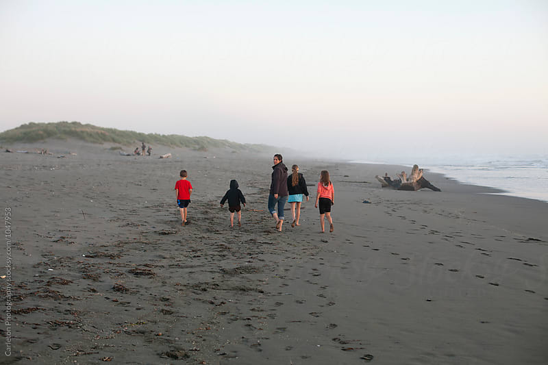 Mom and four kids walk down the beach, mom looks back by Carleton Photography for Stocksy United
