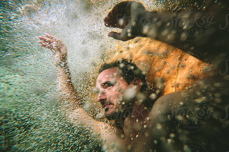 Portrait of a peaceful calm man floating underwater surrounded by bubbles by Jonathan Caramanus for Stocksy United