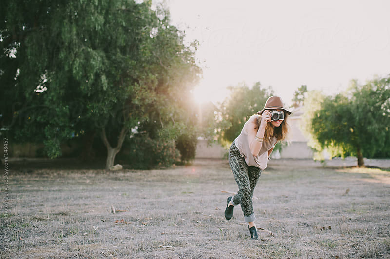 Woman being playful with hat on holding camera by Kristin Rogers Photography for Stocksy United