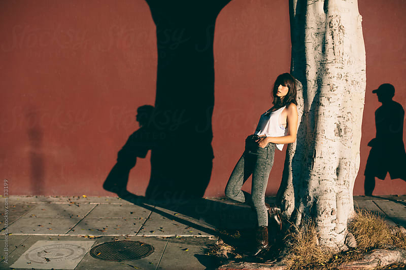 A young woman leaning against a tree by Ania Boniecka for Stocksy United