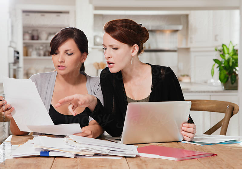 Two young women doing paperwork at kitchen table by Andersen Ross Photography for Stocksy United