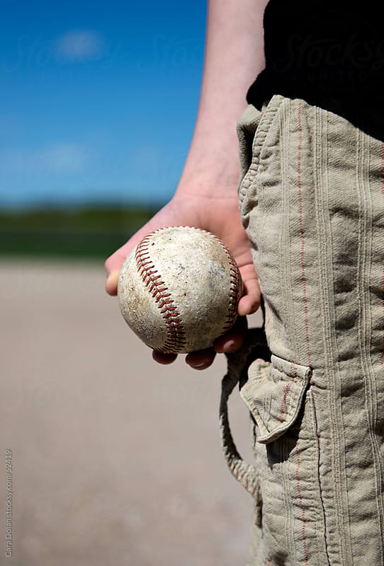 Boy's hand holding old baseball by Cara Dolan for Stocksy United