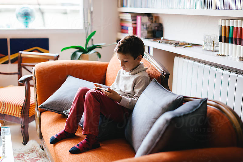 Kid using a smartphone sitting on the couch. by BONNINSTUDIO for Stocksy United