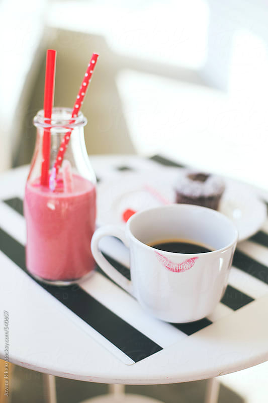 Coffee cup with lipstick print and strawberry smoothie drink on a white table by Jovana Rikalo for Stocksy United