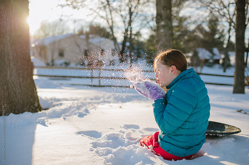 A young teenage girl plays in the snow in a patch of light. by Kelsey Gerhard for Stocksy United