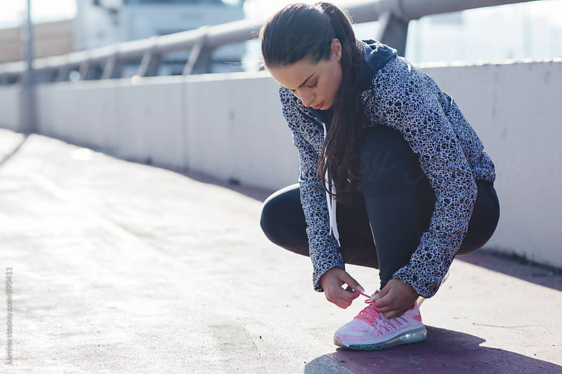 Sportswoman Tying Laces on Sneakers by Lumina for Stocksy United