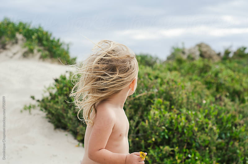 Little girl with windswept hair at beach by Dominique Chapman for Stocksy United