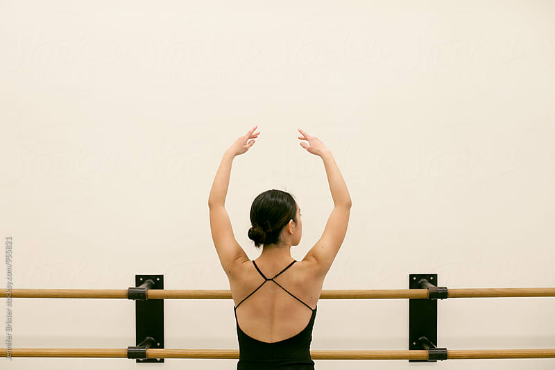 A woman arches her arms by Jennifer Brister for Stocksy United