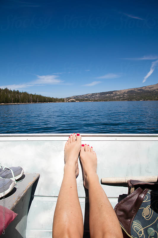 Woman's legs inside a metal fishing boat on a lake with a view by Carolyn Lagattuta for Stocksy United